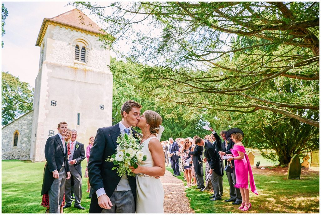 bride and groom kissing whilst friends and family stand behind them during summer wedding