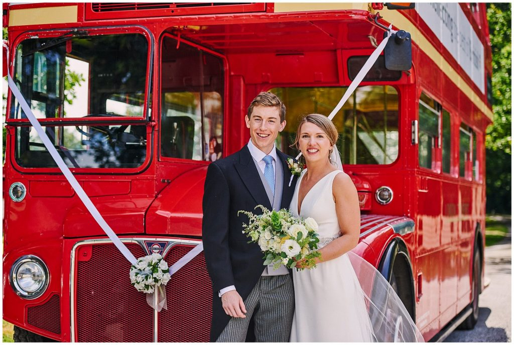 Wedding couple smiling whilst stood in front of a London Red Bus