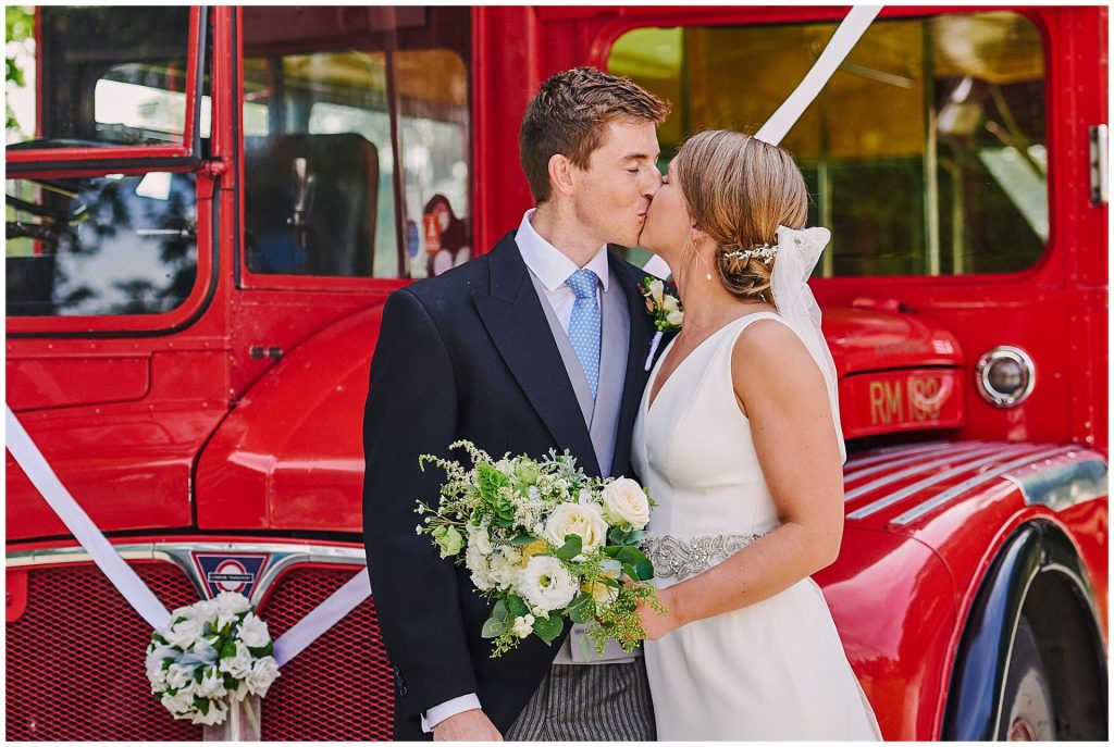 Beautiful wedding couple kissing in front of vintage red bus on a sunny day