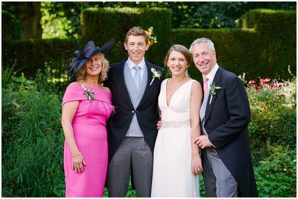 happy bride and groom posing with parents during their festival style Pamber Place wedding.