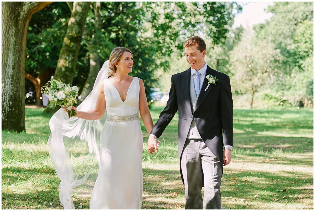 Wedding couple smiling as they walk outside together during their Pamber Place Wedding
