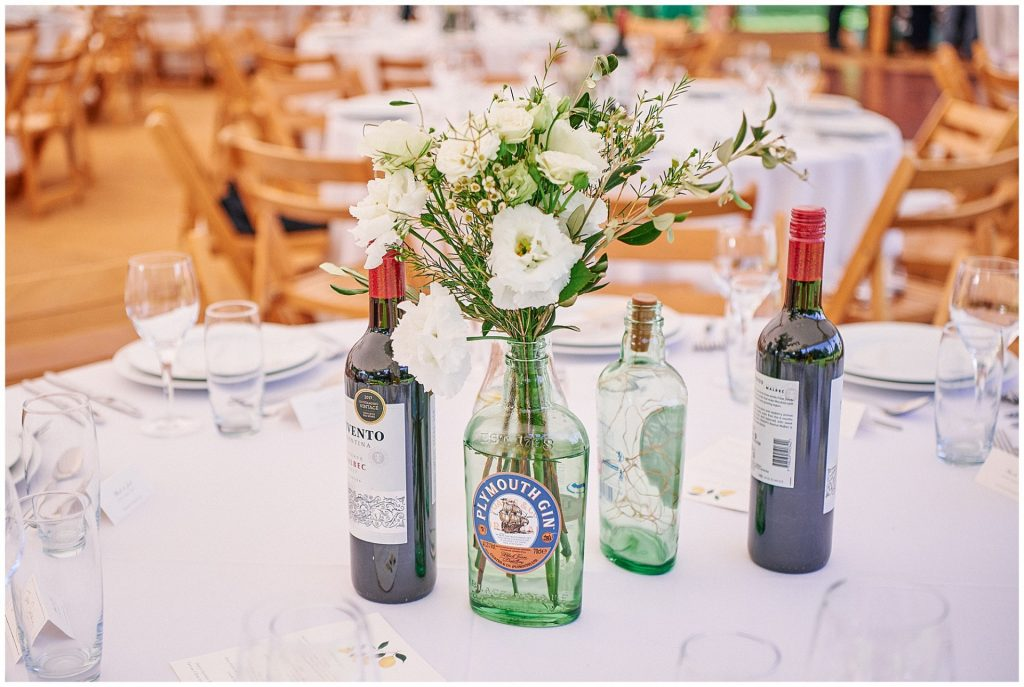 flower and gin bottle table details at a Pamber Place wedding