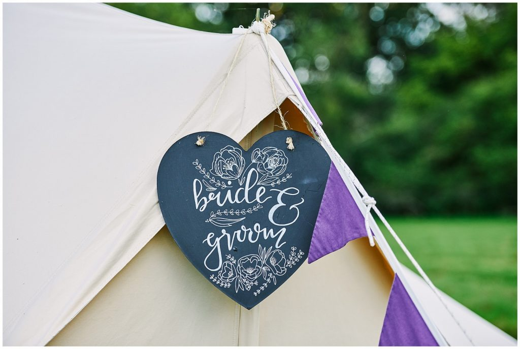 bride and groom chalk board heart hanging on festival bell tent at Pamber Place