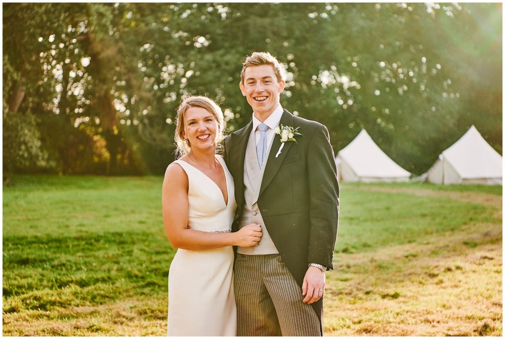 bride and groom smiling during beautiful sunset at their Pamber Place Wedding