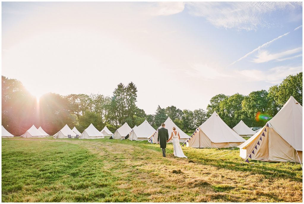 bride and groom walking past tents whilst the sun is setting over their festival wedding