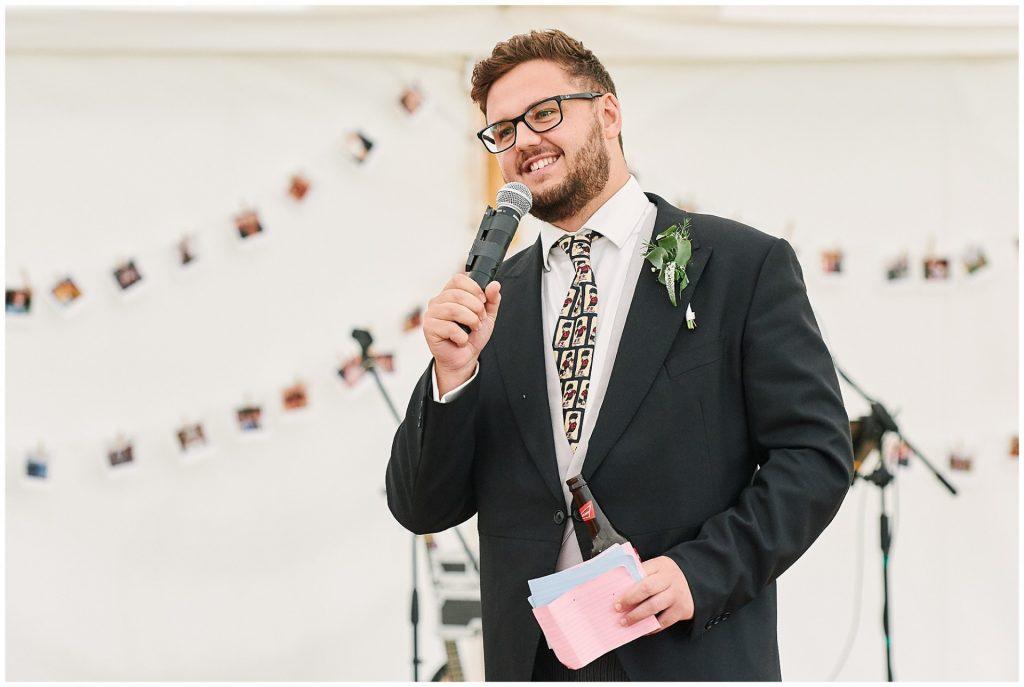 Best man giving a speech during a marquee summer wedding at Pamber Place