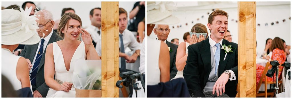 Bride and groom sat in a marquee tent laughing during Pamber Place wedding speeches