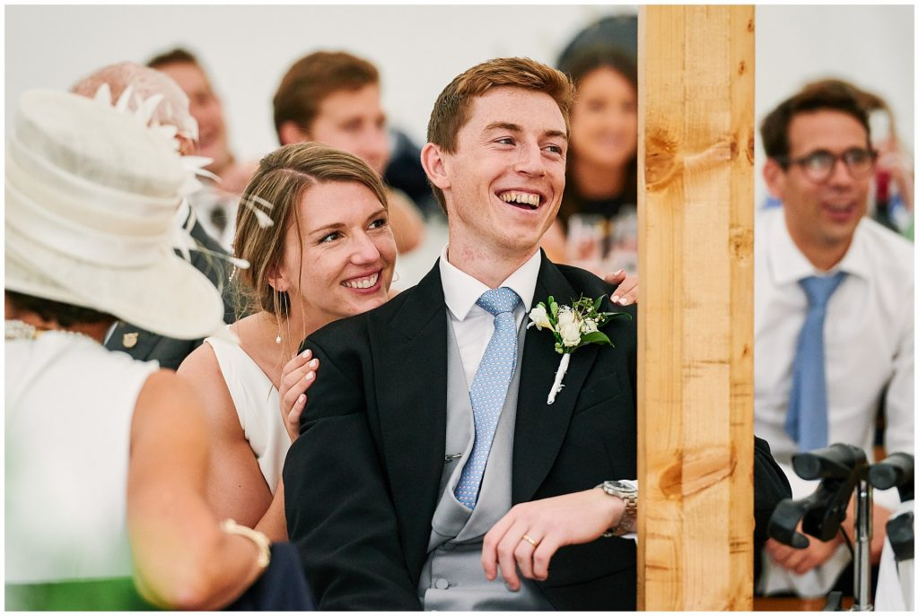 Bride and groom sat together in a marquee tent laughing during wedding speeches