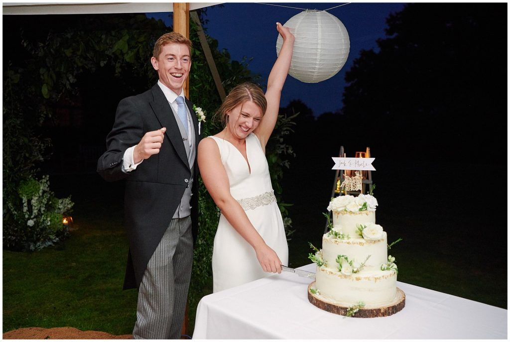 Bride and groom celebrating as they cut their wedding cake at night