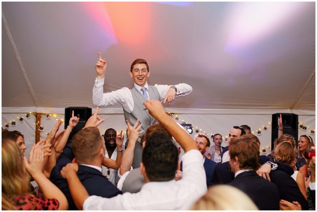 Groom being lifted in the air by dancing wedding guests in marquee