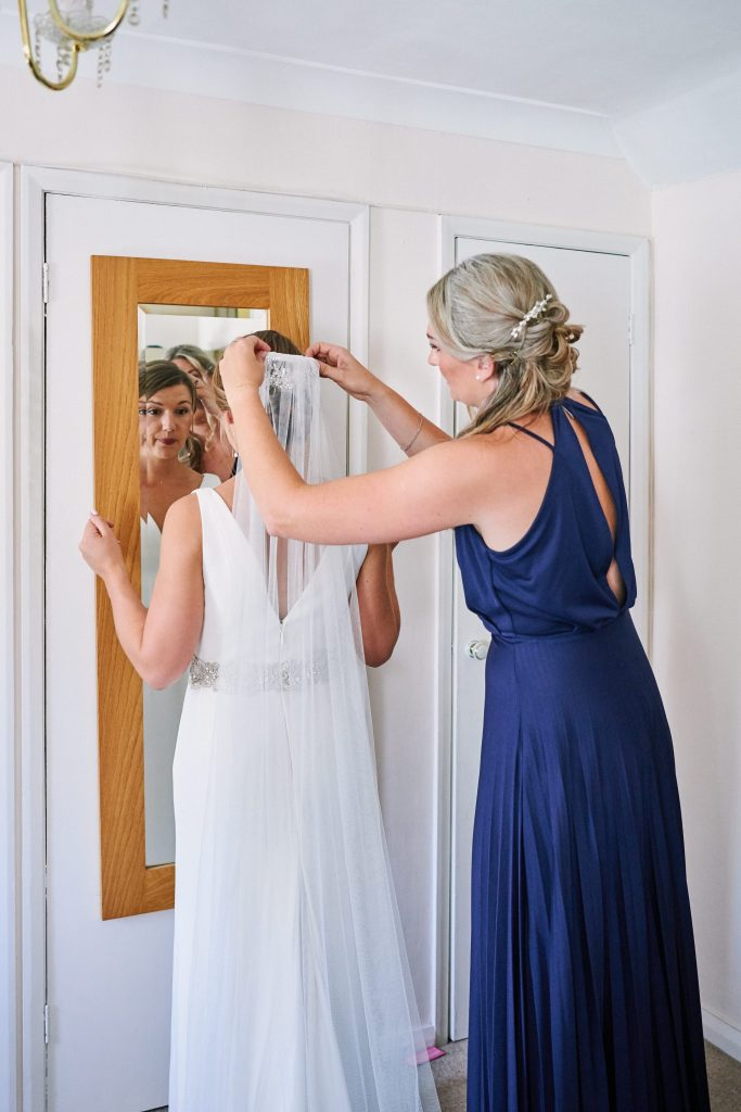 bride having her veil put in by her bridesmaid