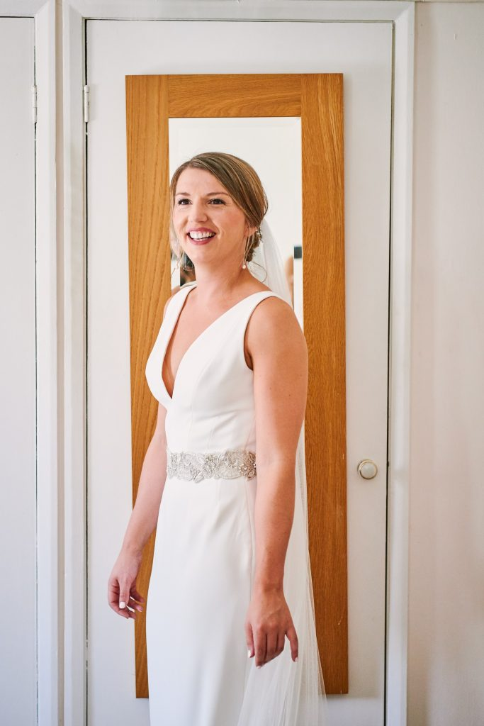 bride laughing in front of mirror in her wedding dress
