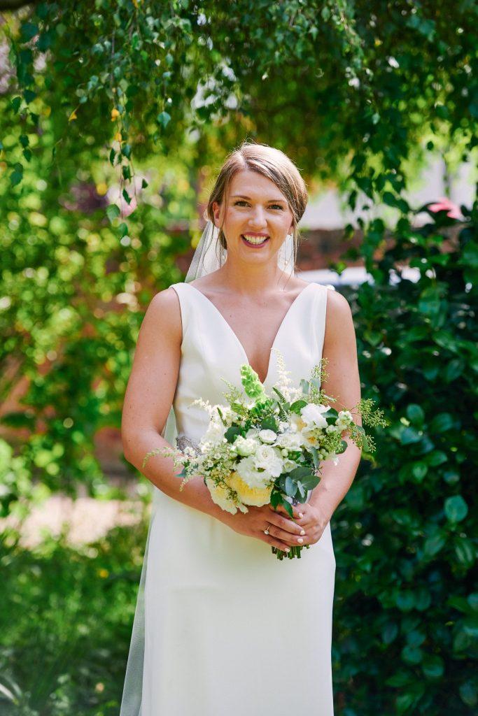 Bride holding beautiful flower bouquet in sunny garden