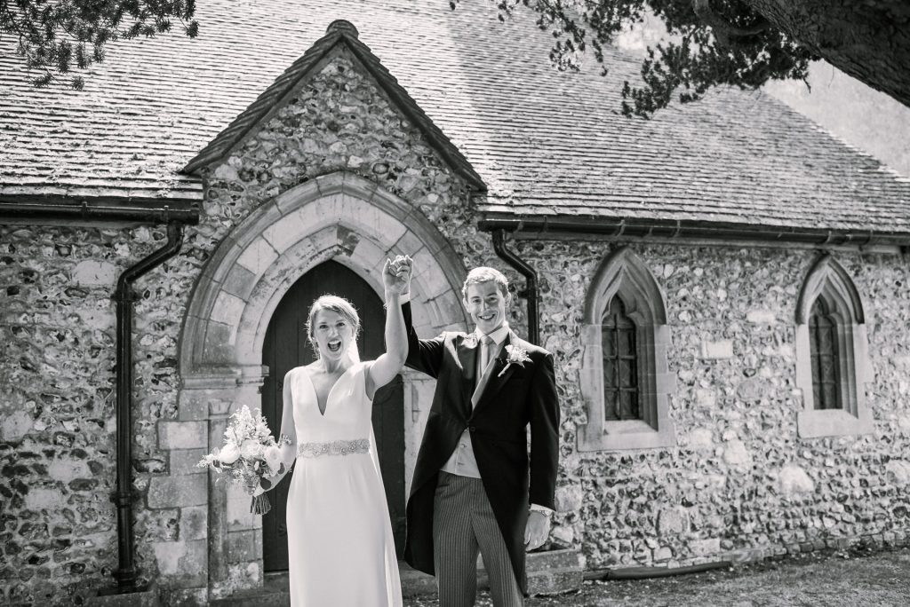 wedding couple celebrating outside of a church after their wedding ceremony
