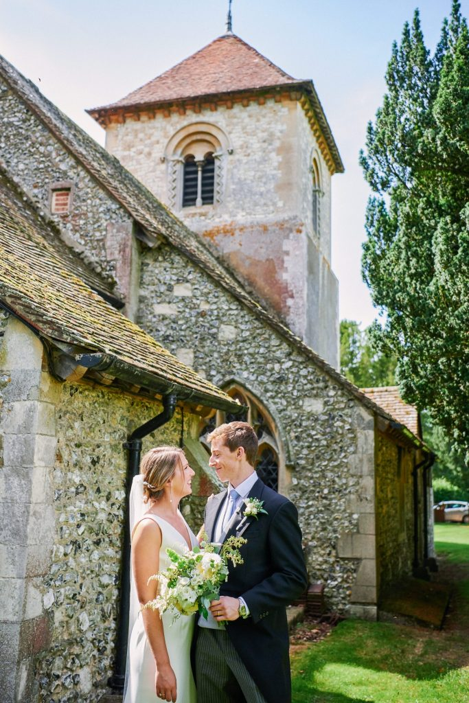 wedding couple smiling at each other outside of a church on a sunny day