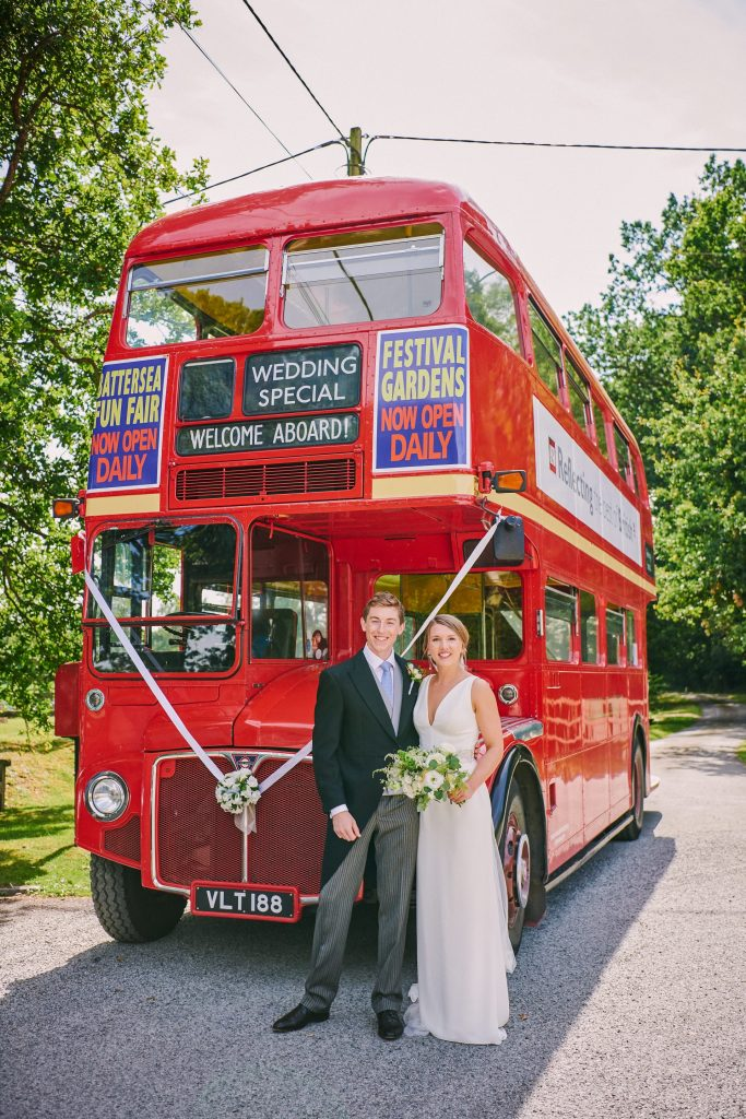 beautiful wedding couple smiling in front of red London bus
