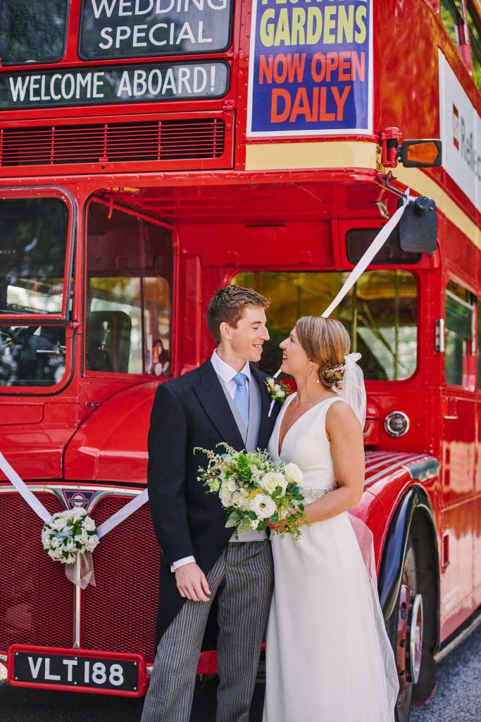 Happy bride and groom in front of red wedding bus