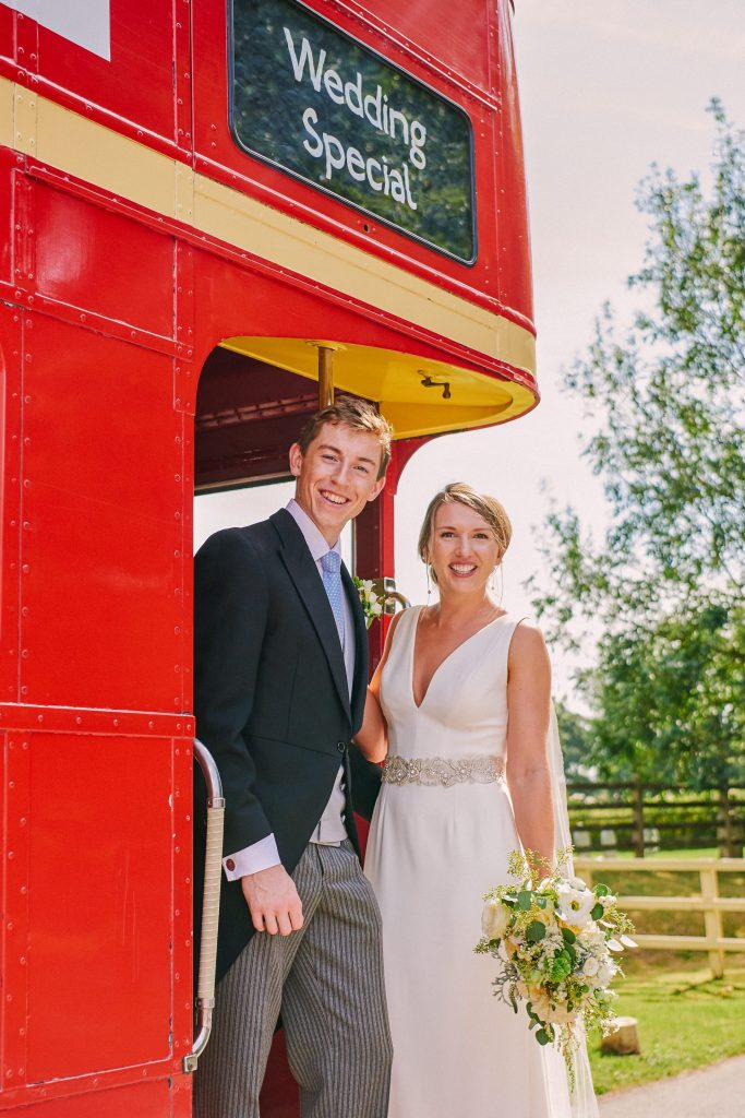 Bride and groom smiling on the back of a red London bus in the countryside