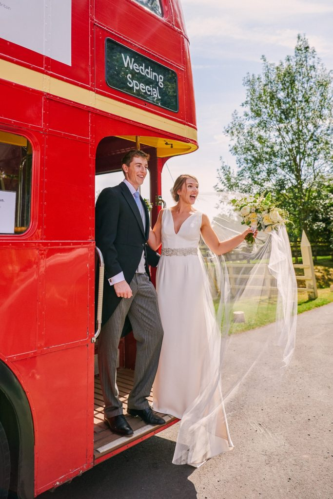 Wedding couple smiling on the back of a red London bus in the countryside