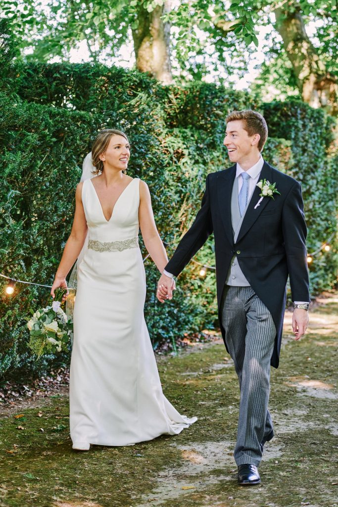 Bride and groom walking together during summer wedding at Pamber Place
