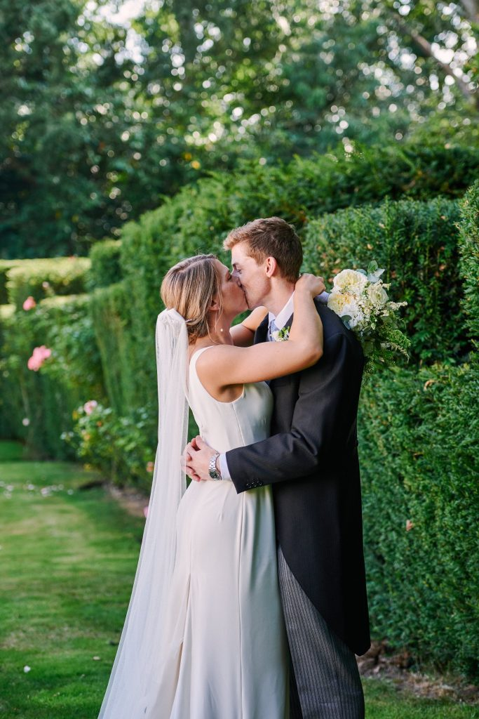 Bride and groom kissing in the garden  during summer wedding at Pamber Place