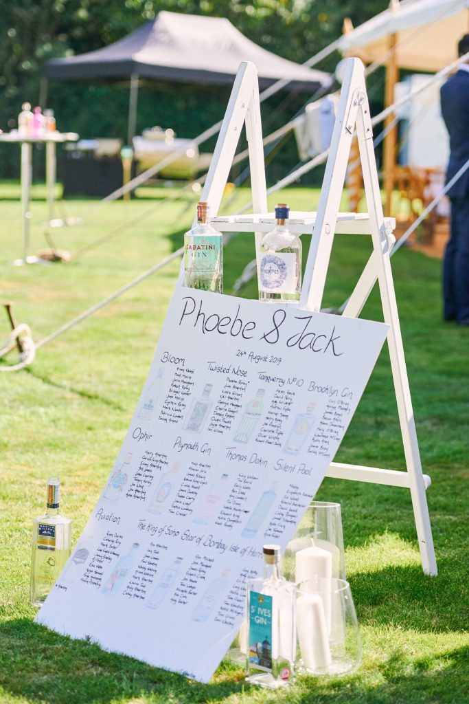 Gin themed table plan at festival style summer wedding