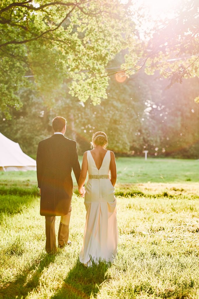 bride and groom walking together at sunset at their beautiful  festival wedding