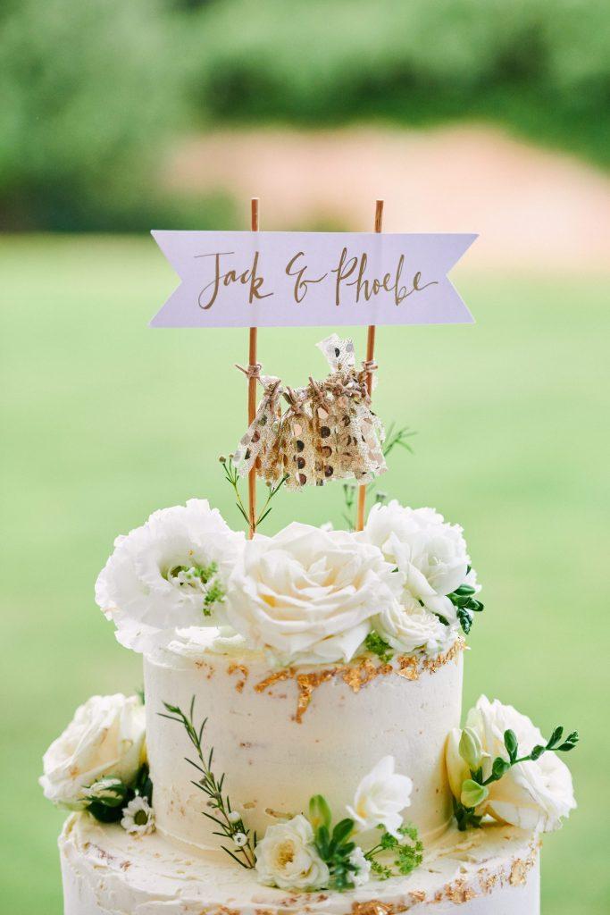 beautiful white rose wedding cake at a summer festival wedding