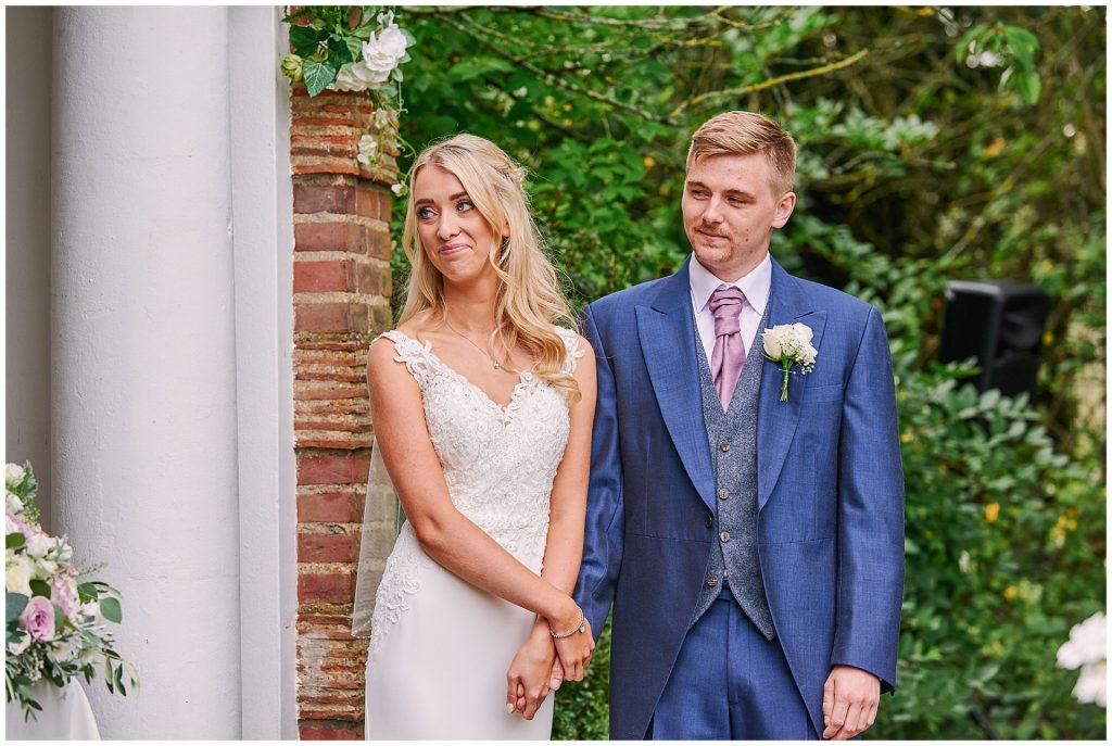 Bride and groom during outdoor garden wedding ceremony at Micklefield Hall