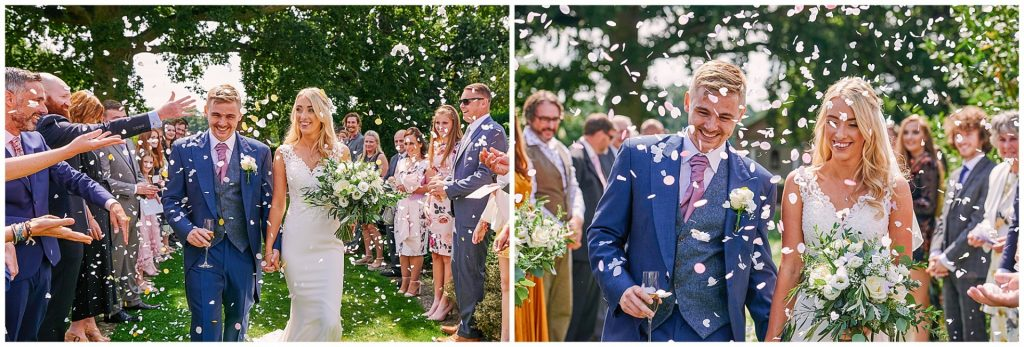 Bride and groom walking through confetti during beautiful outdoor garden wedding at Micklefield Hall