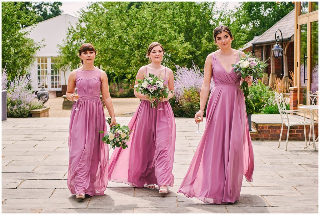 Beautiful bridesmaids in pink dresses walking through the courtyard Micklefield Hall