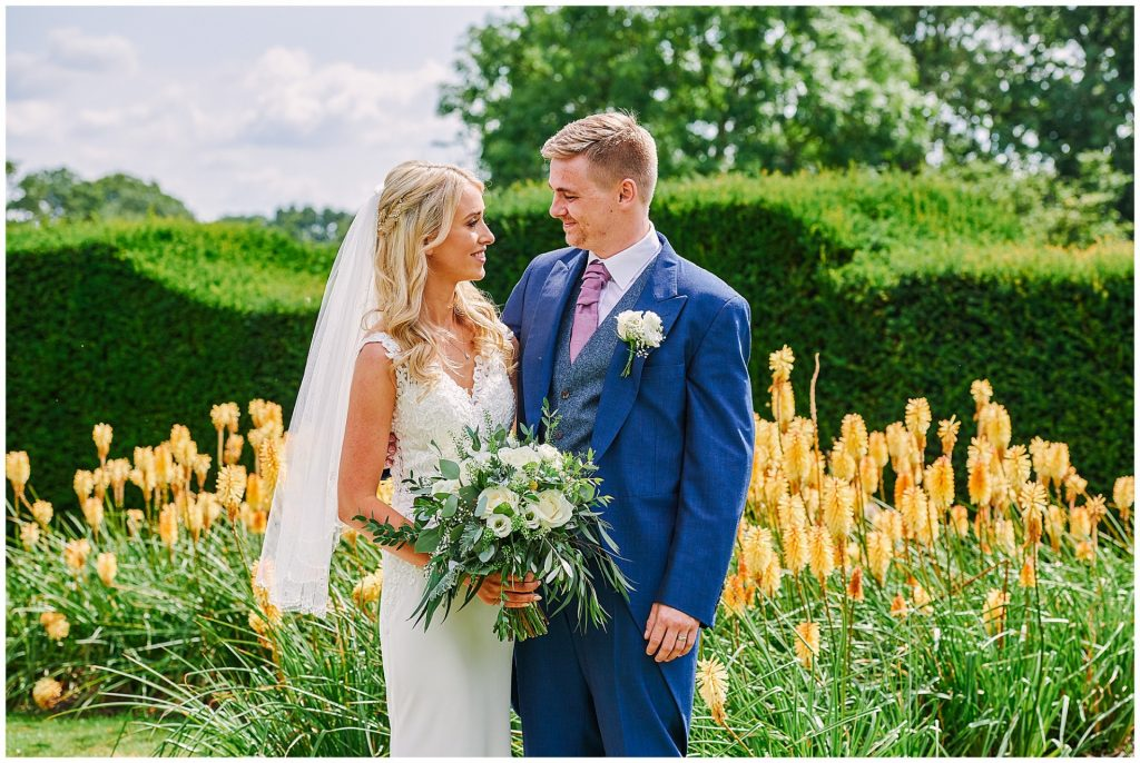 Bride and groom stood in front of yellow flowers in the garden at Micklefield Hall