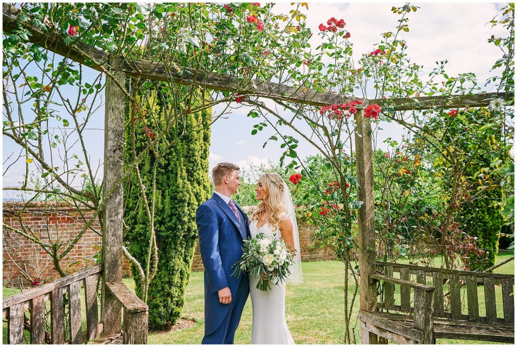 Happy bride and groom stood in a  beautiful outdoor rose garden