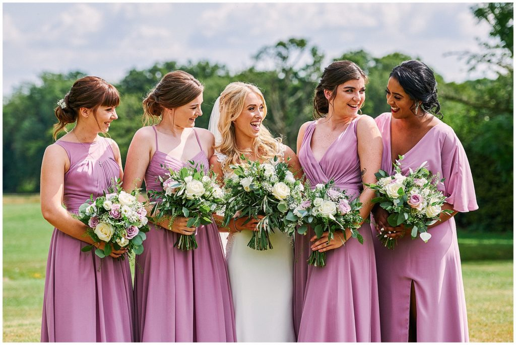Beautiful bride stood outside laughing with her bridesmaids on a sunny day