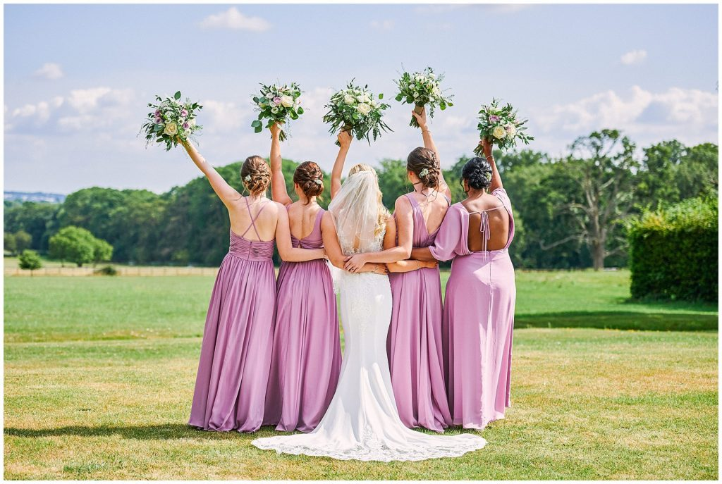 Bride stood with her bridesmaids on a sunny day holding their flowers in the air