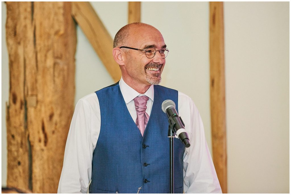 Father of the bride smiling during his wedding speech in a barn