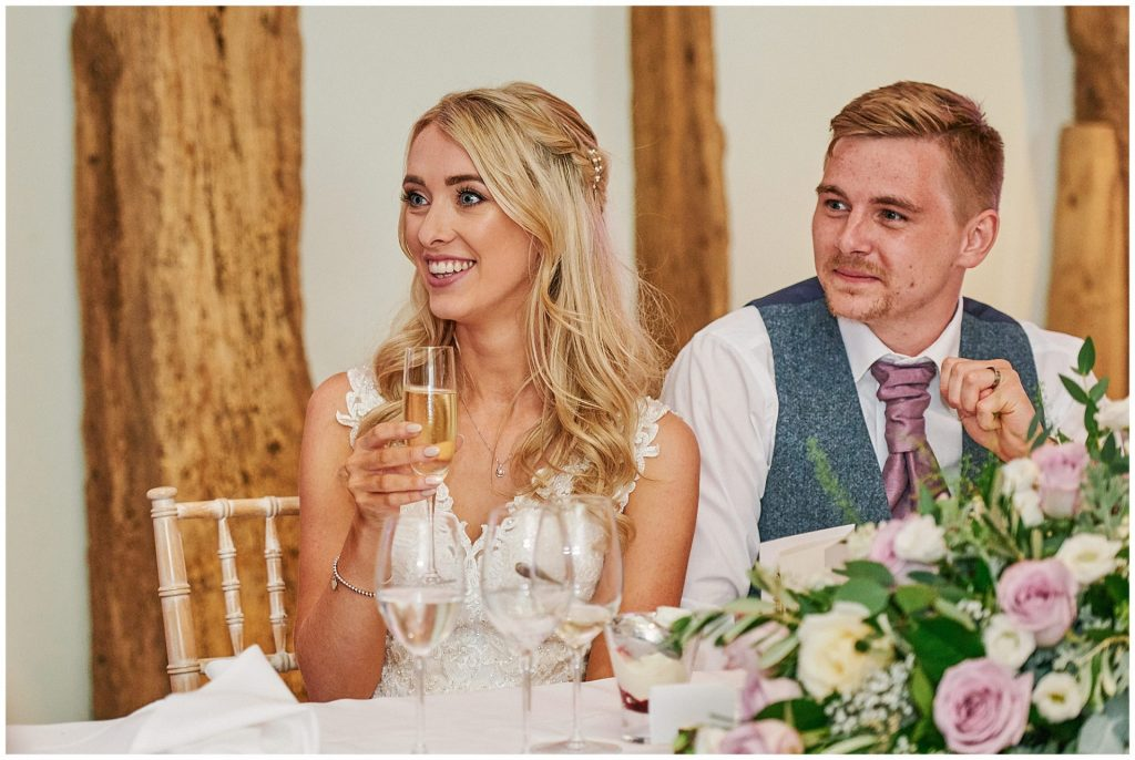 bride and groom sat in a barn smiling during speeches