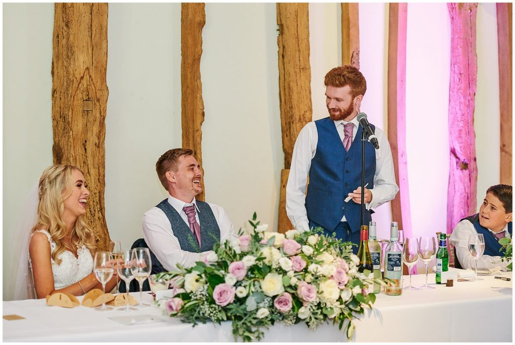 bride and groom sat in a barn laughing during best man speech