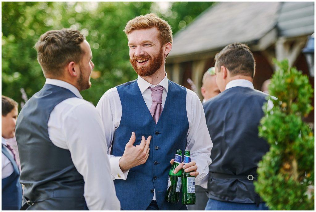 Best man laughing whilst holding beer during outdoor summer wedding at Micklefield Hall