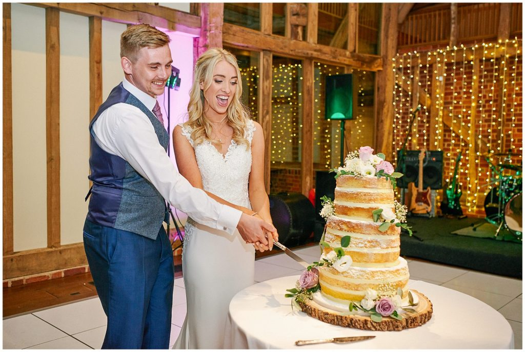 Bride and groom laughing whilst cutting their wedding cake at Micklefield Hall