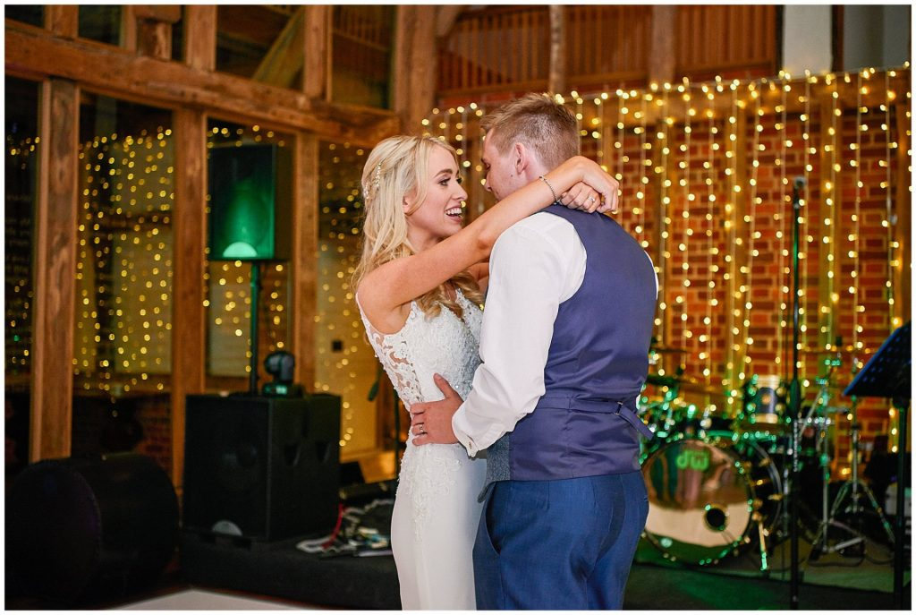 Bride and groom dancing together in front of fairy lights at Micklefield Hall