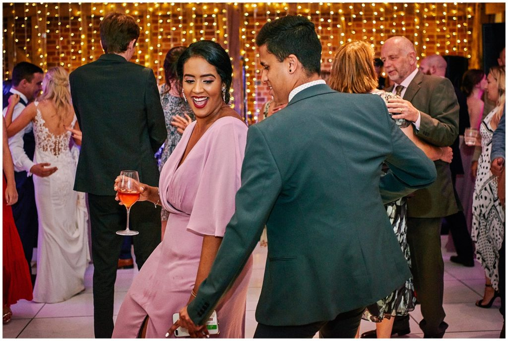 Wedding guests dancing together in front of fairy lights at Micklefield Hall