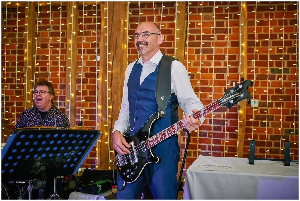 Father of the bride playing guitar on stage during the evening reception at Micklefield Hall