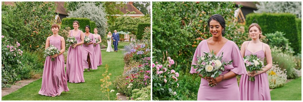 Bridesmaids wearing lilac coloured dresses as they walk down the outdoor garden aisle