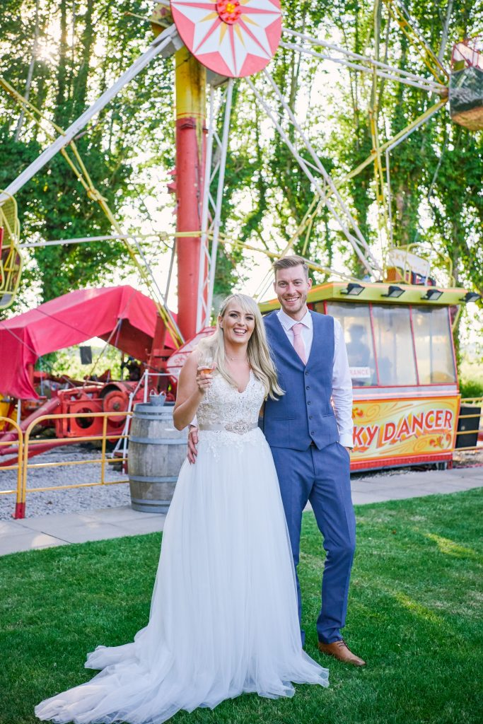 Bride and groom stood in front of vintage funfair ride at unique wedding