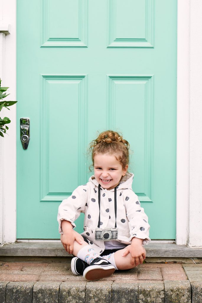Young girl sat smiling in front of her family doorstep