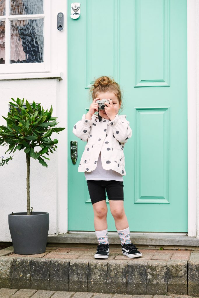 Young child pretending to take a photo in front of her house