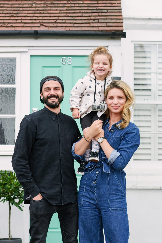 Family stood in front of their front door in East London