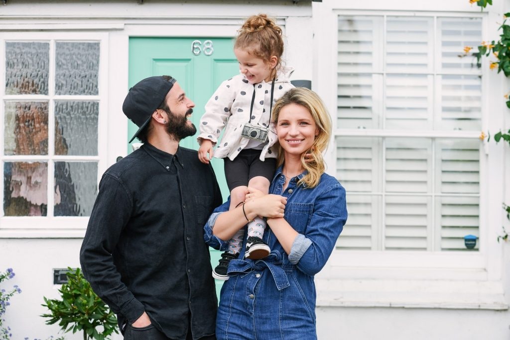 Happy family stood in front of their front doorstep in Loughton, Essex