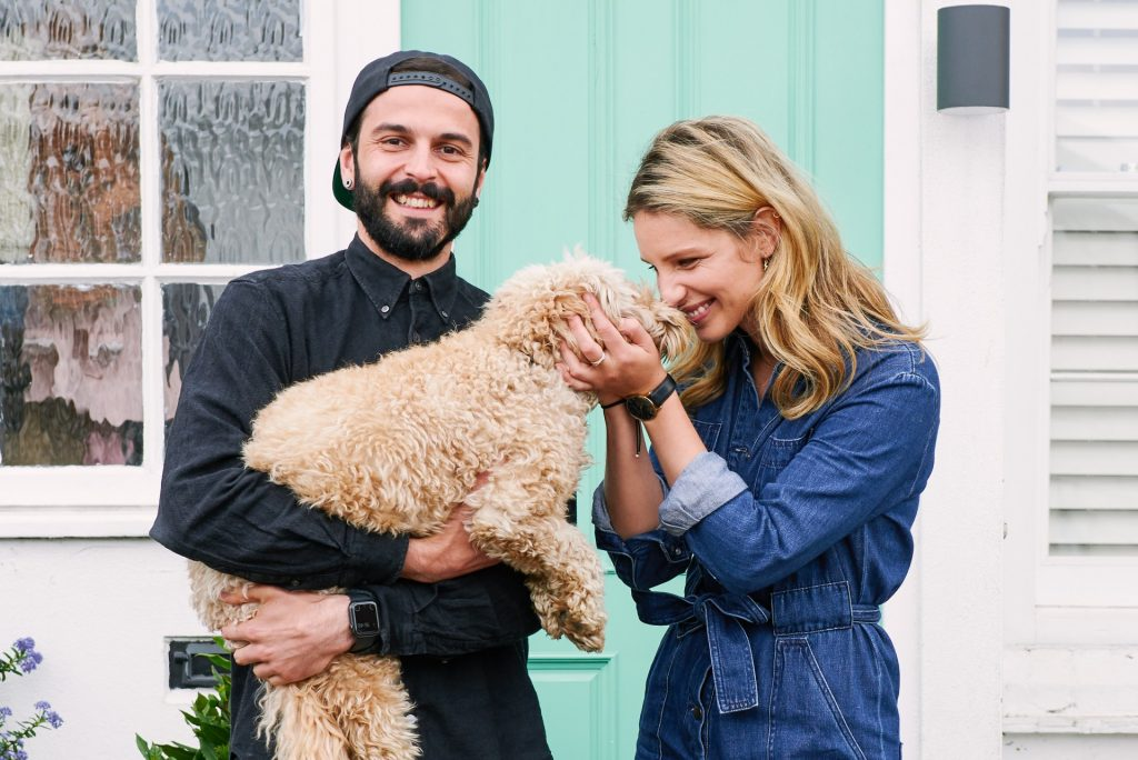 Couple stood with their dog in front of their doorstep in Loughton